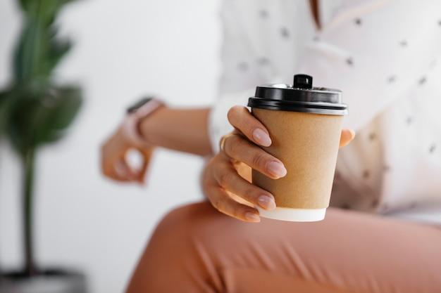 Женщина, держащая макет кофейной чашки