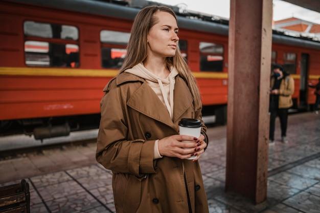 駅でコーヒーを持っている女性
