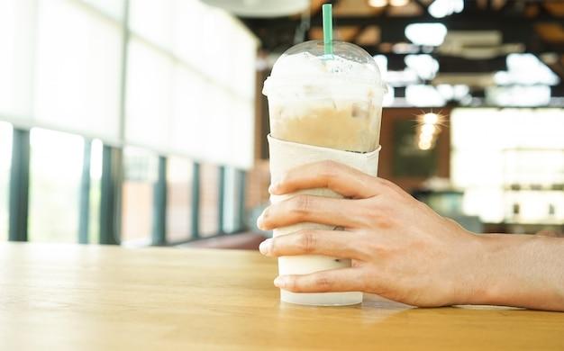Женщина держит холодный кофе на деревянном столе в кафе на отдыхе