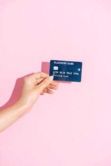 ピンクの背景にクレジットカードを保持している女性