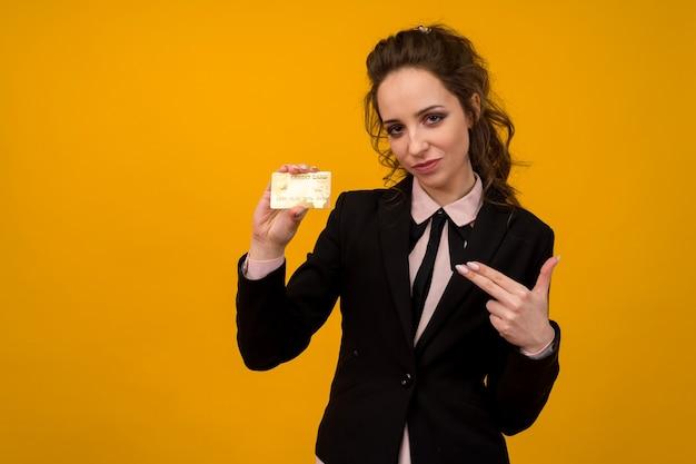 黄色の背景で隔離のクレジットカードを保持している女性