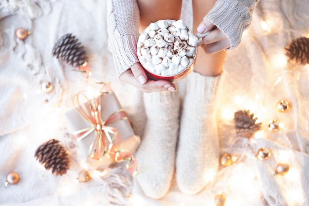 クリスマスの飾りが付いているベッドの上のマシュマロとココアのカップを保持している女性