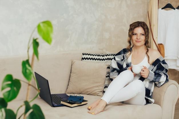 여자가 커피 한 잔을 들고 소파에 앉아 프리미엄 사진