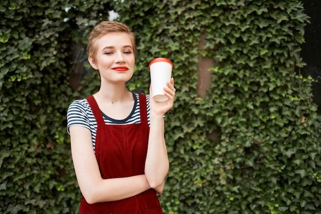 茂みの夏休みの近くの通りで彼女の手にコーヒーを持っている女性