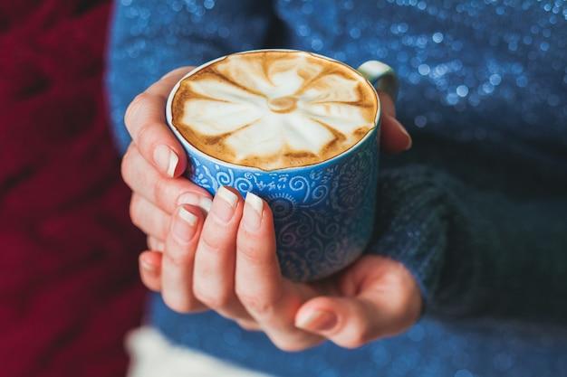 Женщина держит чашку кофе латте с красивым узором