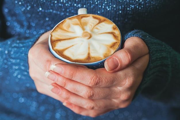 아름다운 패턴으로 커피 라떼 한 잔을 들고 있는 여자