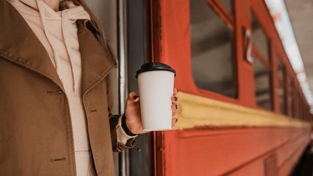 電車の横にコーヒーを持っている女性
