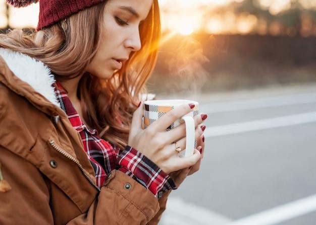 冬の日没の光の中で蒸気と熱い飲み物のカップを保持している女性。