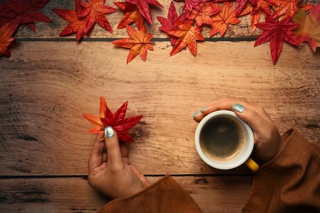 뜨거운 커피와 단풍나무 한 잔을 들고 있는 여자는 나무 테이블에 나뭇잎. 가 시즌 개념입니다.