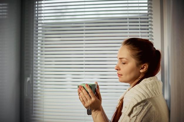 お茶を持って、窓の周りに座って飲んでいる女性。