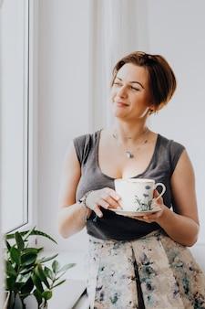 창가에서 차 한 잔을 들고 있는 여자