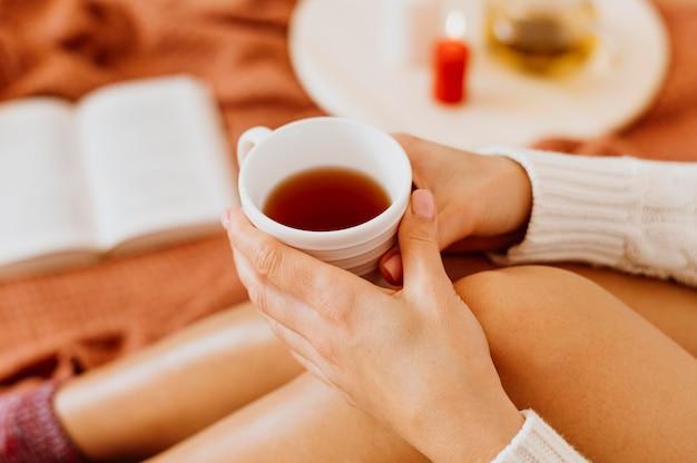 Женщина держит чашку чая