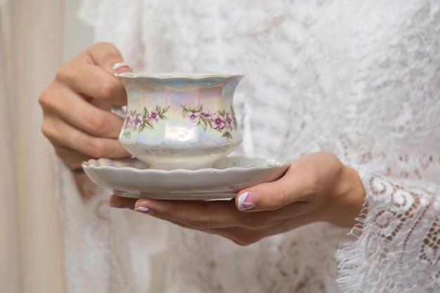 ホットドリンクとカップを保持している女性