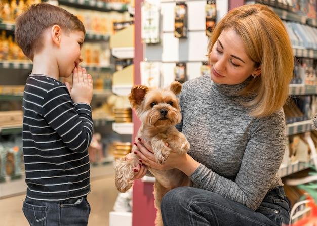 ペットショップでかわいい小さな犬を抱いている女性