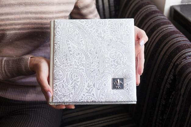 Женщина, держащая семейную фотокнигу. свадебный или семейный фотоальбом в обложке из натуральной кожи. белый цвет с декоративным тиснением.