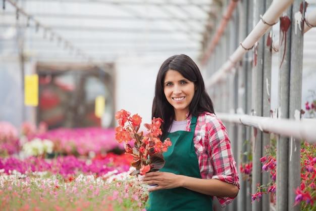 温室で働く花を持つ女性