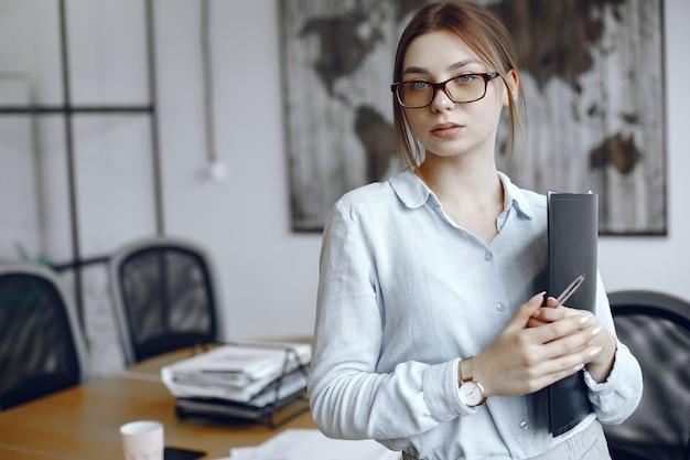 フォルダーを持っている女性。女の子はメガネでカメラの美しさを見ています。