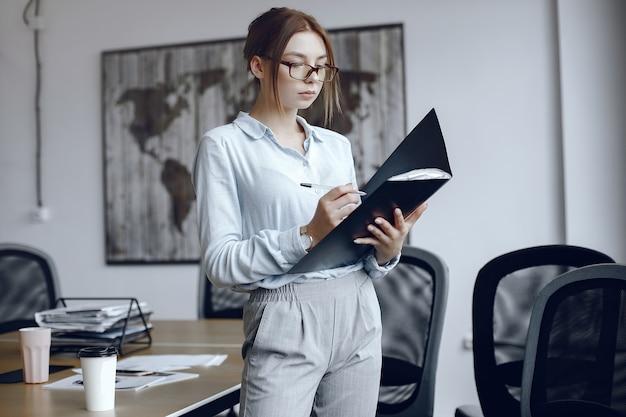 フォルダーを持っている女性。女の子が書類に署名します。メガネの美しさ。