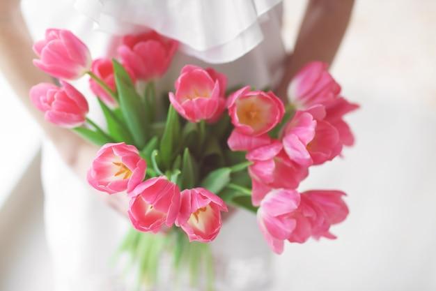チューリップの新鮮な花束を持っている女性。
