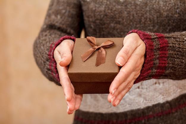그녀의 손에 선물 상자를 들고 여자입니다. 필드의 얕은 깊이, 상자에 선택적 초점. 휴일이나 생일에 선물을 주는 개념.