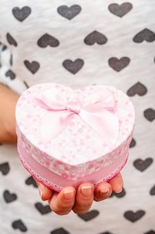 하트 모양의 선물 상자를 들고 있는 여자. 필드의 얕은 깊이, 상자에 선택적 초점. 휴일이나 생일에 선물을 주는 개념.