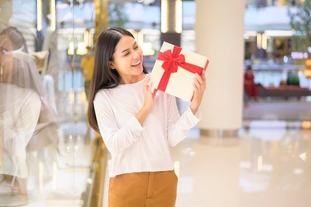 Женщина, держащая подарочную коробку в торговом центре