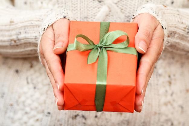 彼女の手で緑のリボンで結ばれたギフトボックスを保持している女性。浅い被写界深度、ボックスに選択的に焦点を合わせます。休日や誕生日に贈り物をするという概念。