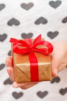 手に赤いリボンで結ばれたギフトボックスを持っている女性。浅い被写界深度、ボックスに選択的に焦点を合わせます。バレンタインデーや誕生日に贈り物をするという概念。