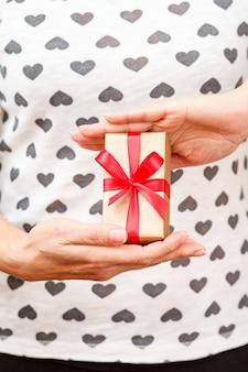 手に赤いリボンで結ばれたギフトボックスを持っている女性。浅い被写界深度、ボックスに選択的に焦点を合わせます。休日や誕生日に贈り物をするという概念。
