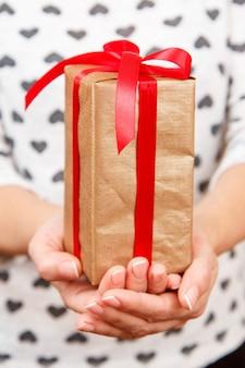 그녀의 손에 빨간 리본으로 묶인 선물 상자를 들고 여자. 필드의 얕은 깊이, 상자에 선택적 초점. 발렌타인 데이 또는 생일에 선물을 주는 개념.