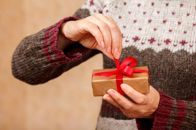 빨간 리본이 달린 선물 상자를 손에 들고 열려고 하는 여자. 필드의 얕은 깊이, 상자에 선택적 초점. 휴일이나 생일에 선물을 주는 개념.