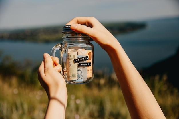 旅行のための節約とガラスの瓶を保持している女性。