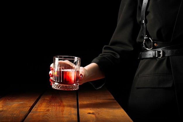 Женщина держит стакан коктейля негрони