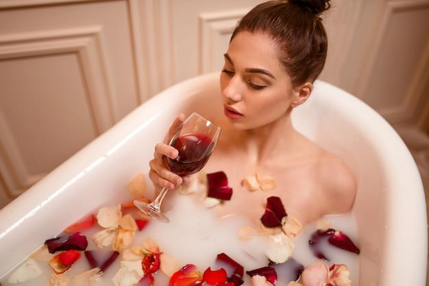 お風呂で赤ワインのガラスを保持している女性