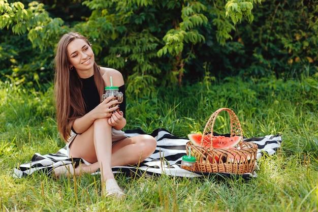 야외 공원에서 피크닉 데 음료와 함께 유리를 잡고 여자