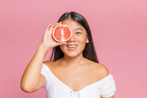 Женщина держит грейпфрут и улыбается
