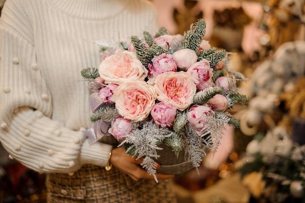 전나무 나무 가지로 장식 된 밝은 분홍색 모란 장미와 회색 스웨터 패턴 상자를 들고 여자