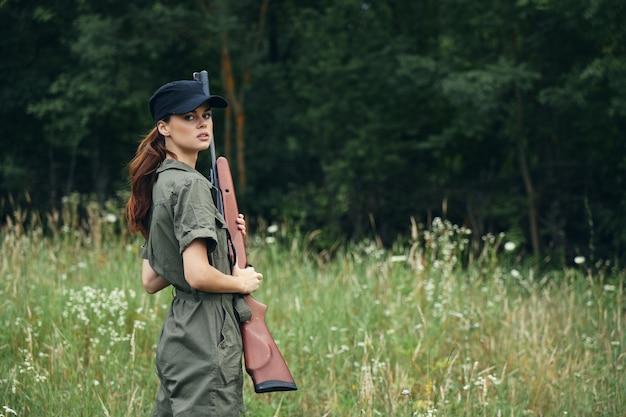 Женщина держит пистолет в руках черная кепка путешествия образ жизни зеленый комбинезон