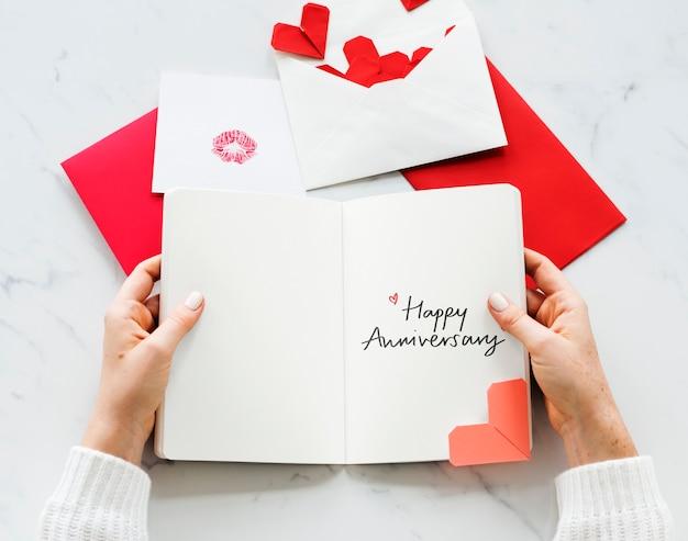 幸せな記念日カードを保持している女性