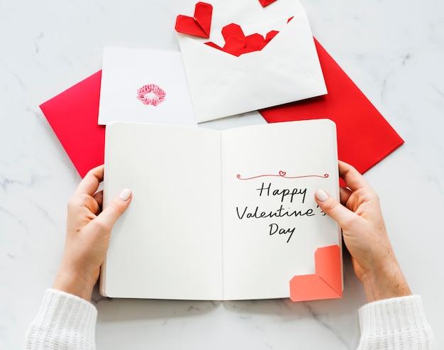 幸せなバレンタインデーのカードを保持している女性