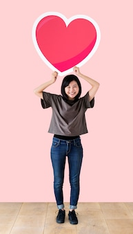 Woman holding a heart emoticon in a studio