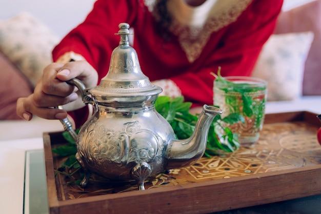 Женщина держит горячий арабский серебряный чайник
