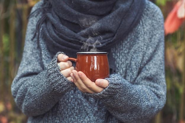 熱いヴィンテージのコーヒーを持っている女性