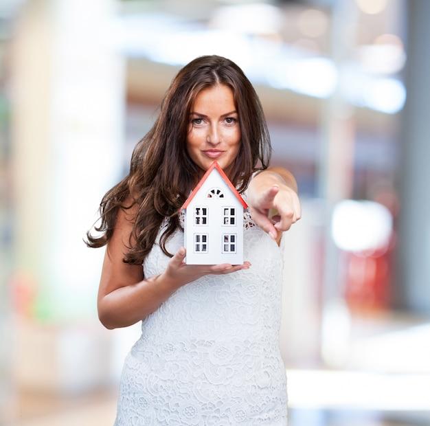Женщина, держащая дом и указывая на передний план