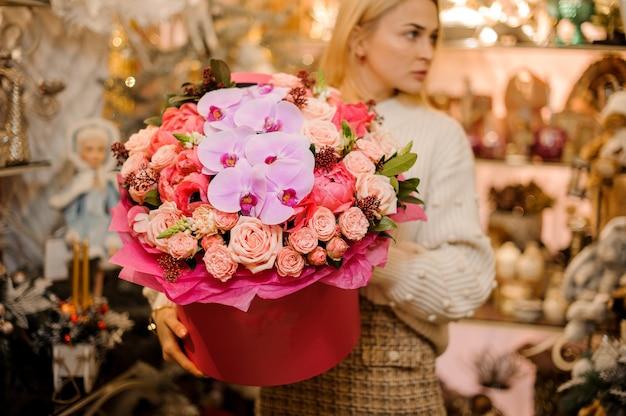 복숭아 색 장미, 밝은 분홍색 난초 및 다른 장미 색 꽃과 함께 거대한 빨간색 상자를 들고 여자