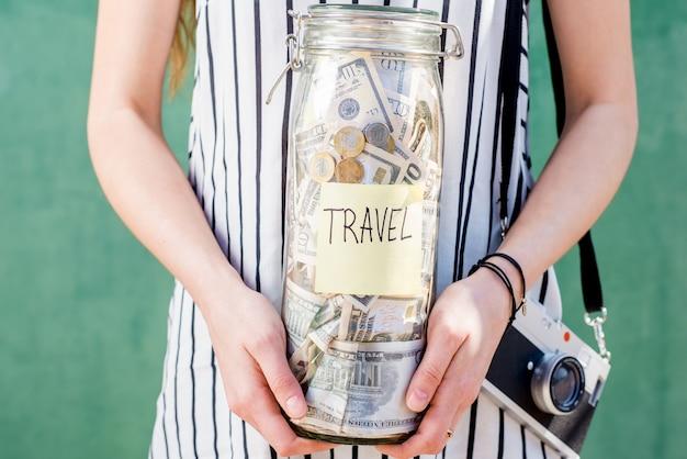 緑の背景に写真カメラで立って旅行のためのお金でいっぱいの瓶を保持している女性。夏休みのコンセプトのためのお金の節約