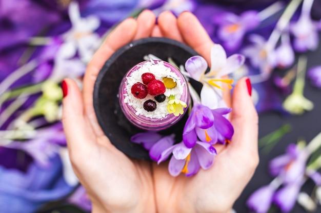 紫色の春の花に囲まれた、ベリーをトッピングしたビーガンスムージーの瓶を持っている女性