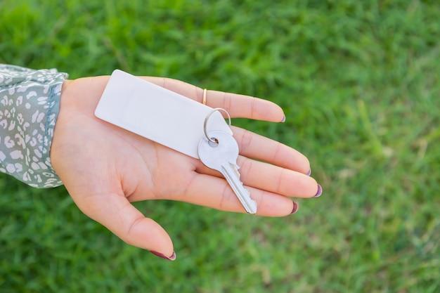 녹색 잔디 배경으로 열쇠 고리를 들고 여자입니다.