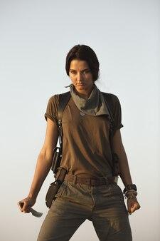 砂漠の屋外でナイフを持っている女性。武器を持った残忍な危険な少女