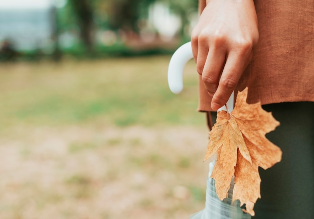 Женщина держит лист и зонтик с копией пространства